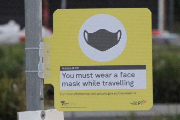 Blunt 'You must wear a face mask while travelling' signage at a bus stop