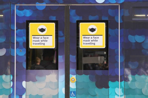 'Wear a face mask while travelling' stickers cover the last remaining section of clear windows on this advertising covered tram
