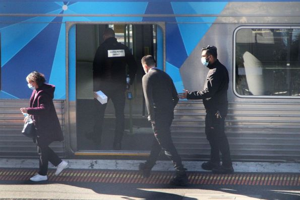 Authorised Officers board a train with a box of disposable face masks