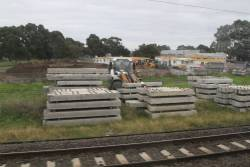 Pile of new concrete turnout bearers at the down end of Dandenong station