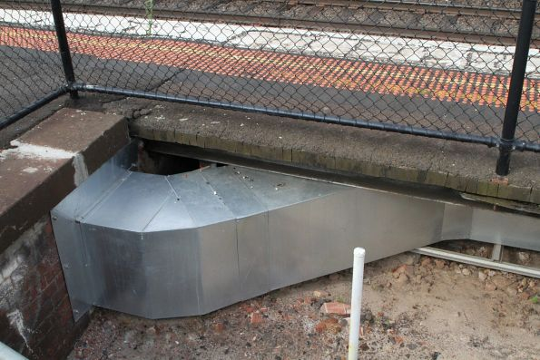 Sheetmetal trough carries signal cables beneath the platform at Armadale station