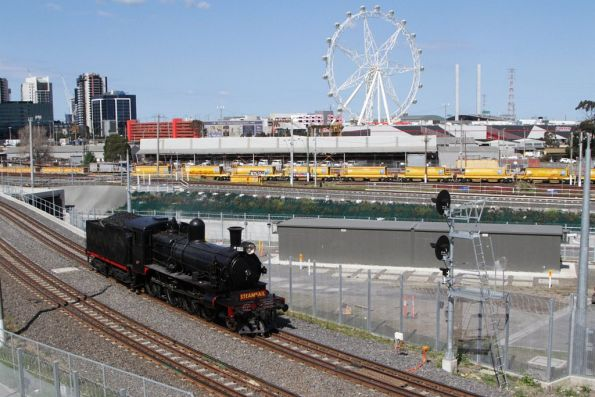 'Melbourne Star' observation wheel in the background as D3 639 heads for Castlemaine