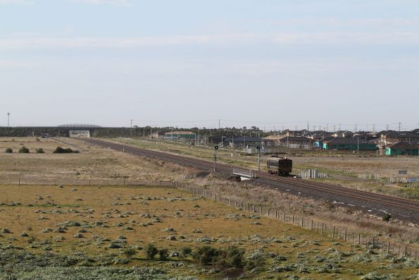 RM58 passes new houses beside the RRL tracks at Tarneit