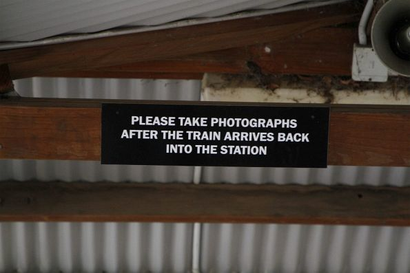 'Please take photographs after the train arrives back into the station' notice
