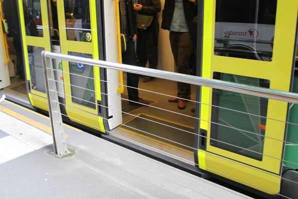 Rear door of an E class tram overhangs the platform stop at Collins and William Street