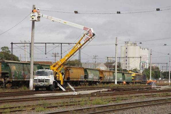 Cherry picker being used to remove overhead wires that are in the way of the crane