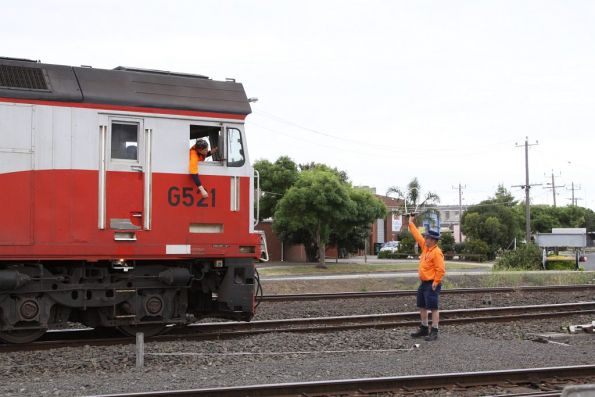 Signaller holds the Train Staff for the Grain Loop, the second person ready to grab hold of it