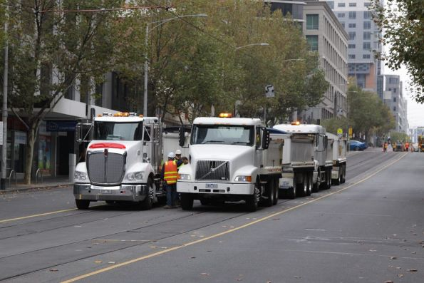 Tip trucks on La Trobe Street, waiting to be loaded with rubble