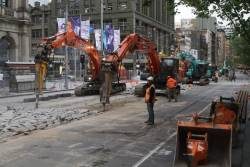 Six excavators breaking up concrete at the corner of Bourke and Elizabeth Streets