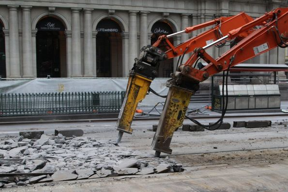 Jackhammer equipped excavators at work breaking up concrete