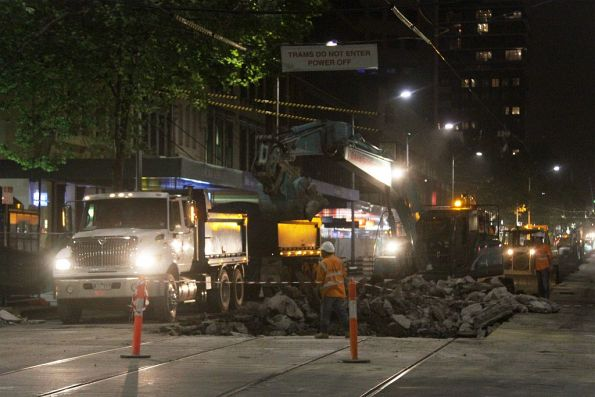 Loading rubble into dump trucks at the corner of Collins and Elizabeth Streets