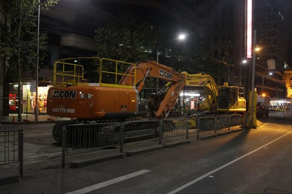 Excavators with jack hammer, parked away from the work zone until they get taken away