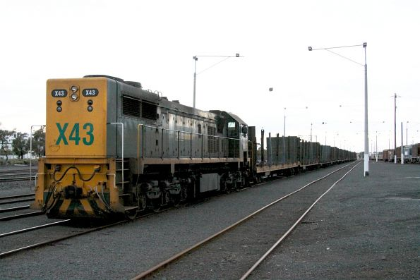 X43 long end leading with a rake of empty log flats stabled at North Geelong Yard, H1 is at the opposite end