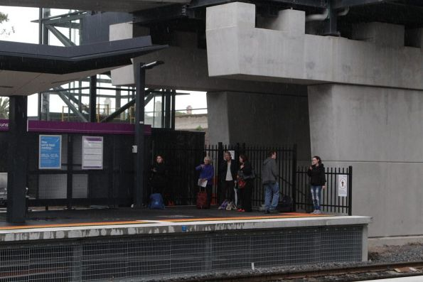 Passengers attempt to find shelter from the wet weather at Sunshine platform 4
