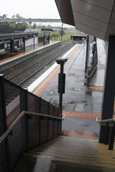Rain covers the stairs between platform and concourse at Sunshine station