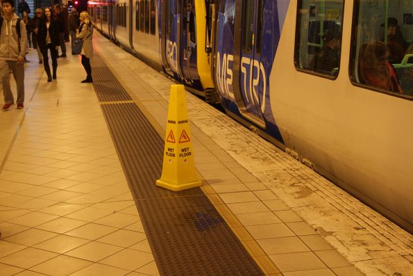 'Caution Wet Floor' sign beneath a leaking veranda at Flinders Street platform 3
