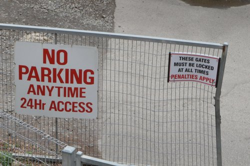 'These gates must be locked at all times' notice on an open set of gates