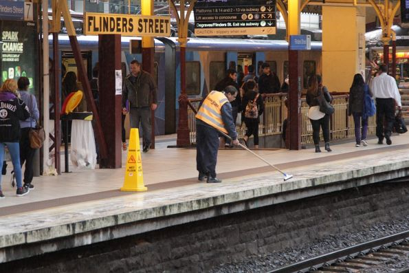 Cleaner sweeping water off the platforms at Flinders Street Station