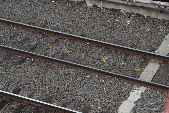 Yellow 'x' marks on what are presumably defective railway sleepers