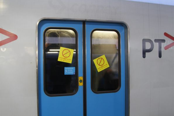'Door not in use' stickers in place on an X'Trapolis train in peak hour