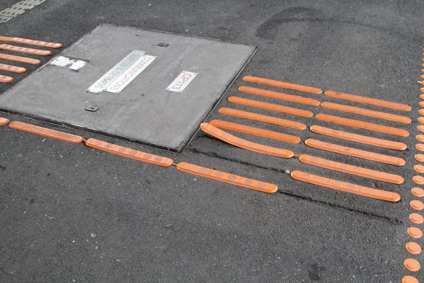 Tactile paving peeling away from the asphalt, forming a trip hazard