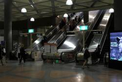 Three escalators running upwards at Flagstaff station, with the fourth out of service