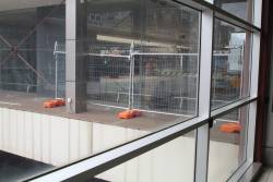 Temporary fencing behind a smashed pane of glass on the main Flinders Street Station concourse