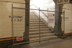 Repainting the handrails around the Degraves Street subway stairs at platform 8 and 9