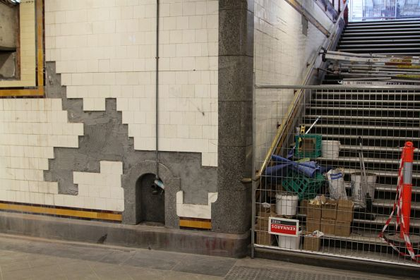 Repairing cracked tiles in the stairway up to platform 8 and 9