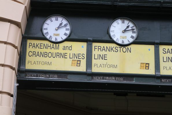 Faded 'Next train for' signs exposed beneath the Flinders Street Station clocks