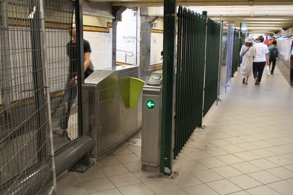 Installing the new glass fence between paid and unpaid areas in the Elizabeth Street Subway