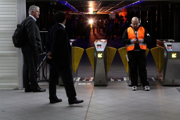 Bouncer on the Degraves Street exit from the station, as some confused commuters look on