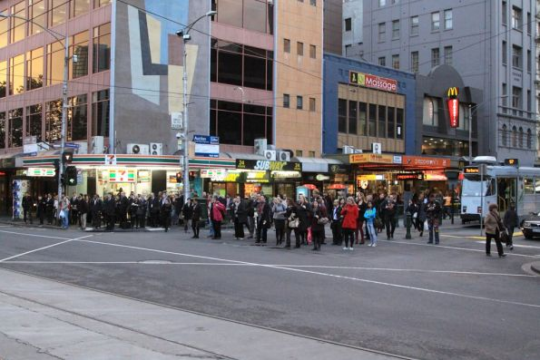 Crowds of commuters wait to cross Flinders Street at Elizabeth Street