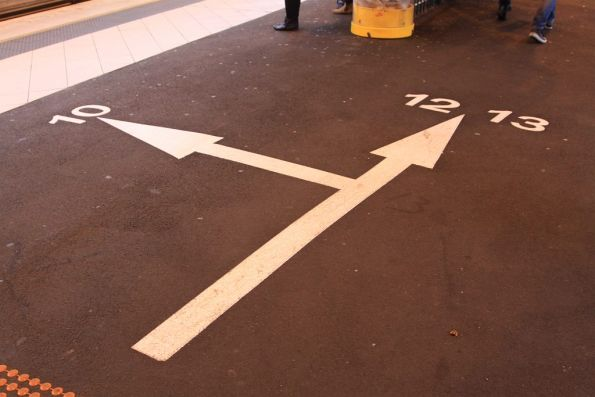 Directional arrows painted on the ground at the west end of platform 10