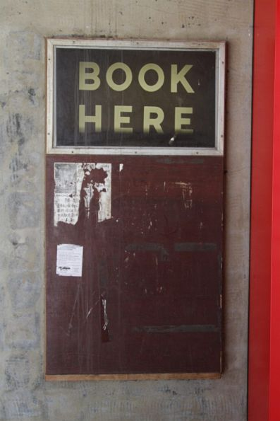 'Book here' sign on a disused booking office window at the Elizabeth Street end of the station
