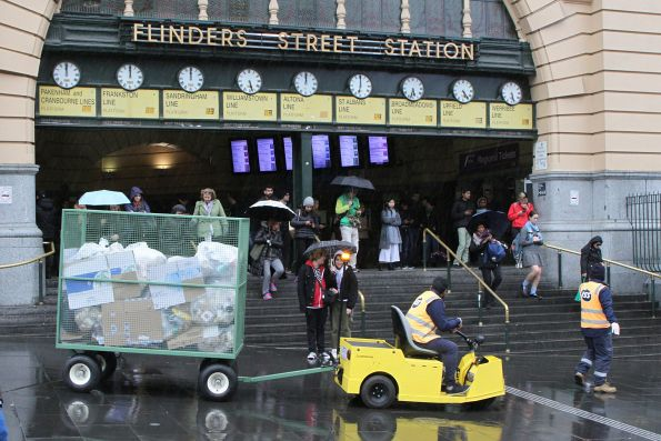 Trolley full of rubbish heads past the clocks at Flinders Street Station
