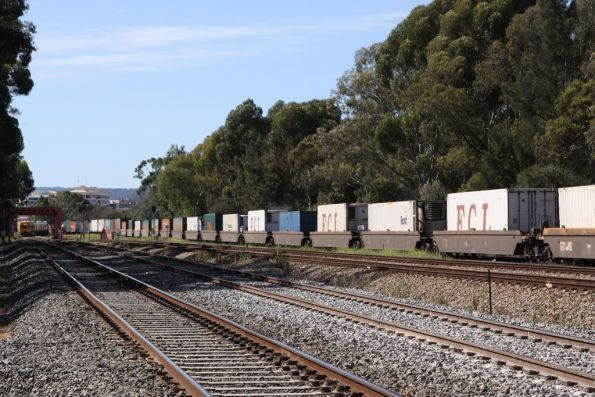 Pacific National well wagons roll past at Torrens Junction