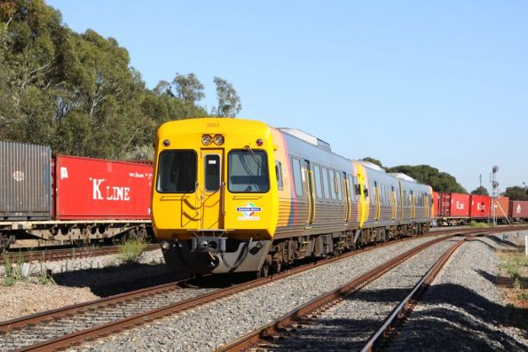 Comeng 3003 trails a Mawson Lakes bound suburban service, passing the QRN freight at Torrens Junction