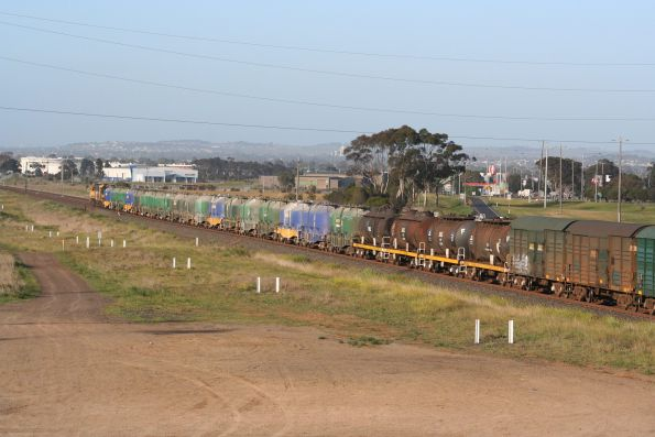 Cement hoppers, oil tankers and louvred vans make up the front half of the train