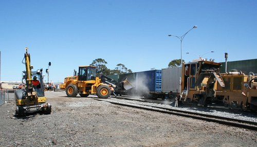 Trackwork continues as a freight train passes on the other track