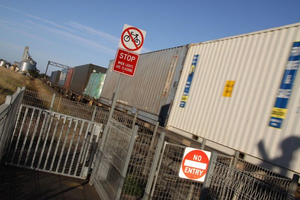 Containers streak past the level crossing