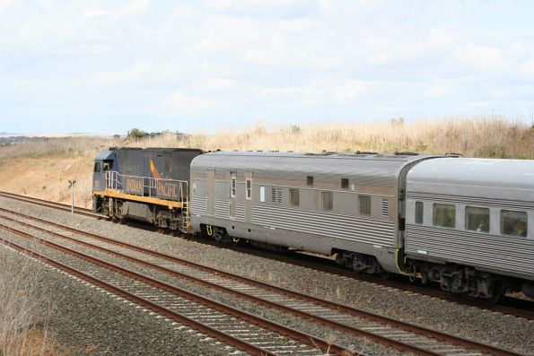 Indian Pacific liveried NR25 on the Adelaide bound Overland outside Little River, with a HGM power van at the lead end