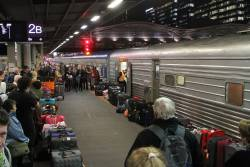The Overland passengers waiting to collect their baggage at Southern Cross