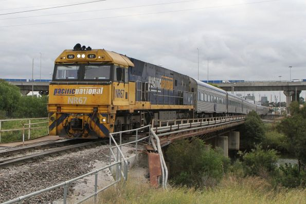 NR67 leads The Overland across Moonee Ponds Creek towards Southern Cross Station