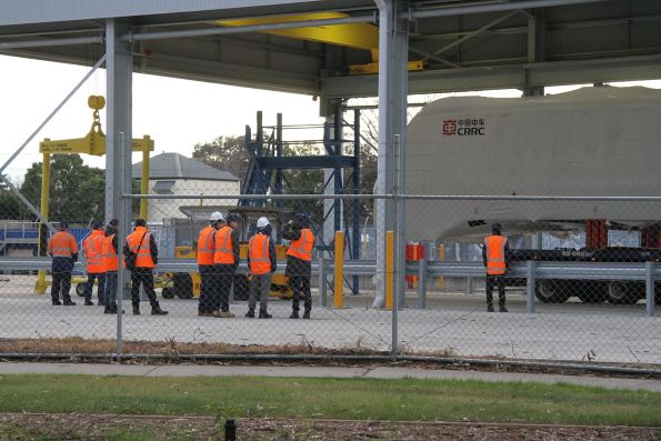 Plenty of onlookers watch the HCMT carriage body reverse into the gantry crane shed