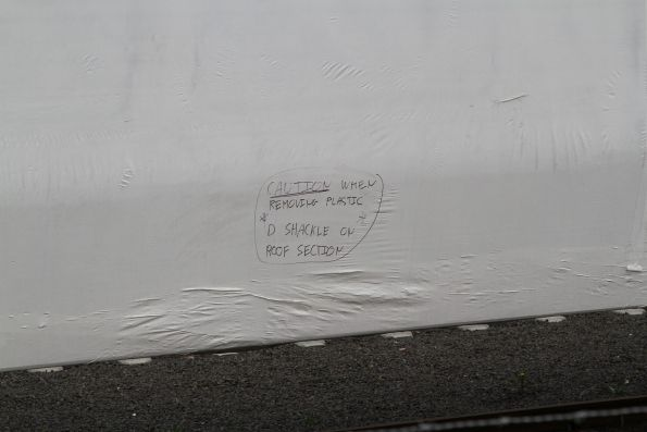 'Caution when removing plastic D shackle on roof section' scrawled on a plastic wrapped HCMT carriage