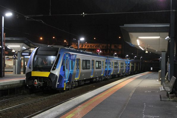 HCMT set departs Footscray station, Franco Cozzo in the background