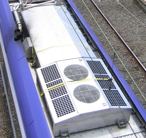 Tie-down straps hold down panels of the roof mounted air-conditioning units
