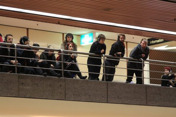 Audience watches from the upper level concourse, listening with wireless headphones