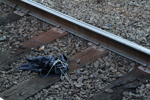 Broken umbrella discarded on the railway tracks